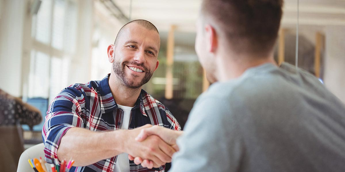 Lächelnder Chef schüttelt die Hand eines Bewerbers